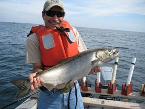 Angler holding a Chinook salmon on a boat on Lake Huron